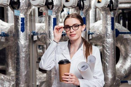 Photo pour Ingénieur gai en manteau blanc et en lunettes tenant des bleus et une tasse de papier près du système d'approvisionnement en air - image libre de droit
