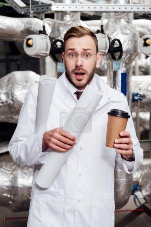 Photo pour Ingénieur effrayé en veste et lunettes blanches tenant des bleus et une tasse de papier près du système d'approvisionnement en air - image libre de droit