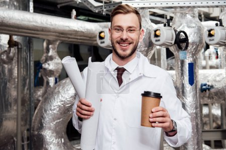 Photo pour Ingénieur joyeux en manteau blanc tenant des bleus et une tasse de papier près du système d'approvisionnement en air - image libre de droit