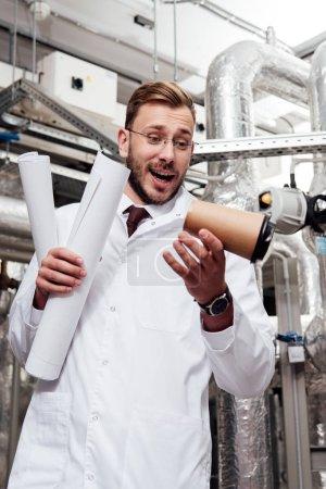 Photo pour Ingénieur inquiet vêtu d'un manteau et de lunettes blancs tenant des bleus et regardant tomber une tasse de papier près du système d'approvisionnement en air - image libre de droit