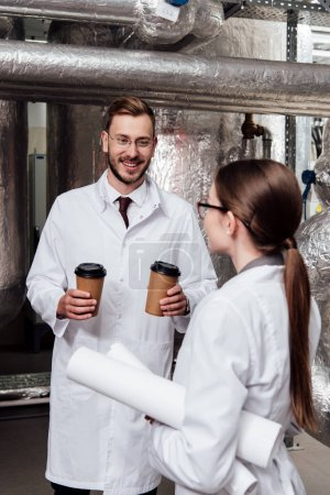 Photo pour Ingénieur heureux tenant des tasses en papier près de collègue dans des lunettes - image libre de droit