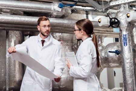 Photo pour Ingénieur en manteau blanc regarde un collègue en lunettes tout en tenant un plan - image libre de droit