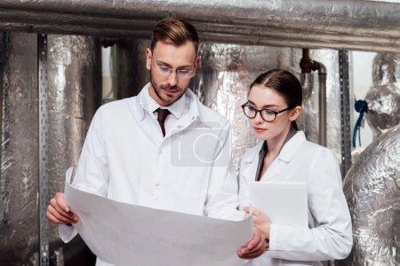 Photo pour Des ingénieurs en manteau blanc regardent un plan - image libre de droit