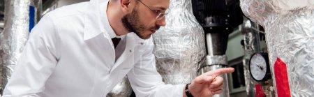Photo pour Photo panoramique d'un ingénieur barbu en manteau blanc tenant une tablette numérique et pointant du doigt vers le système d'alimentation en air - image libre de droit