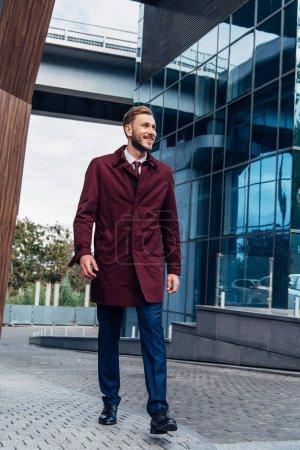 Photo pour Homme barbu gai en manteau marchant dans la rue - image libre de droit