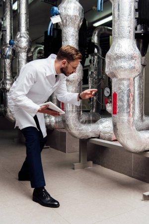 Photo pour Ingénieur en veste blanche tenant la tablette numérique et pointant du doigt vers le système d'alimentation en air - image libre de droit