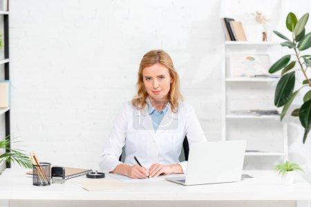 Photo pour Nutritionniste attrayant assis à la table et tenant stylo dans la clinique - image libre de droit