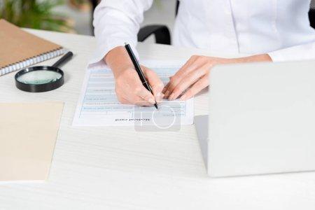 Photo pour Crochet vu d'une nutritionniste assise à une table et remplissant une carte médicale dans une clinique - image libre de droit
