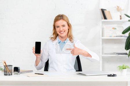 Photo pour Nutritionniste souriant assis à table et pointant du doigt le smartphone avec espace de copie à la clinique - image libre de droit