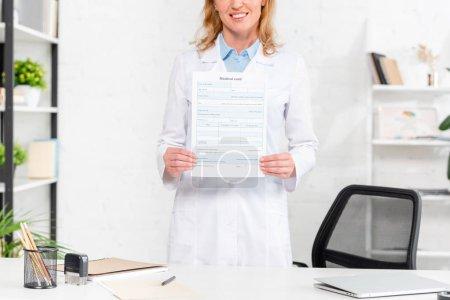 Photo pour Crochet vue d'une nutritionniste souriante tenant une carte médicale dans une clinique - image libre de droit