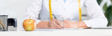 Photo pour Prise de vue panoramique de pomme sur la table et nutritionniste assis à la table et écriture sur fond à la clinique - image libre de droit