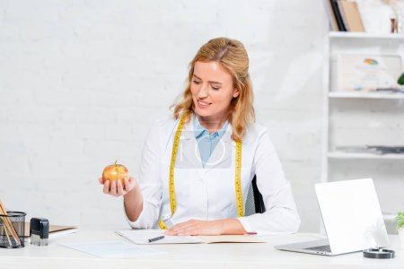 Photo for Smiling nutritionist sitting at table and holding apple in clinic - Royalty Free Image
