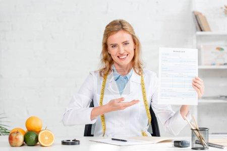 Photo pour Nutritionniste souriant assis à table et pointant la main vers la carte médicale à la clinique - image libre de droit