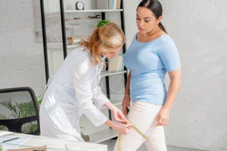 Photo pour Nutritionniste attrayant mesure jambe du patient avec ruban à mesurer en clinique - image libre de droit