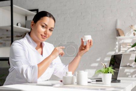 Photo pour Dermatologue attrayant assis à table et pointant du doigt la crème cosmétique à la clinique - image libre de droit