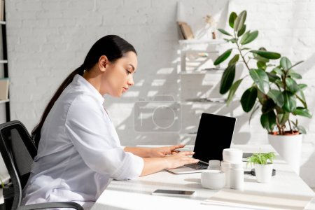 Photo for Attractive dermatologist sitting at table and using laptop in clinic - Royalty Free Image