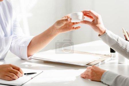 Photo pour Vue recadrée du dermatologue donnant de la crème cosmétique au patient en clinique - image libre de droit