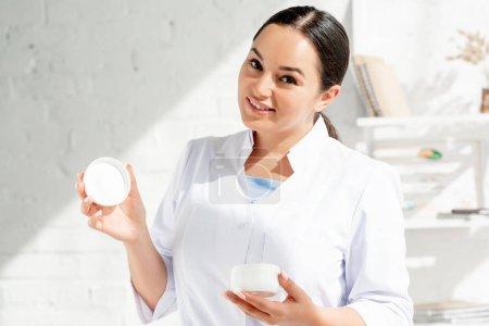 Photo pour Dermatologue souriant tenant crème cosmétique et regardant la caméra à la clinique - image libre de droit