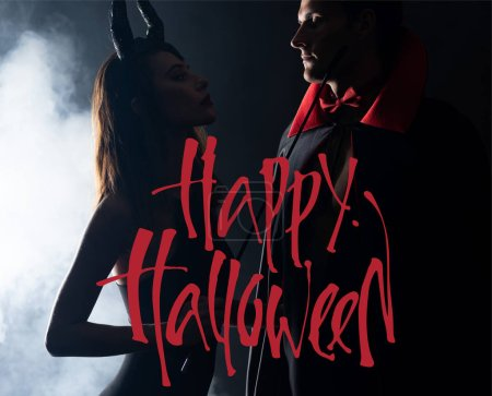 Photo pour Bel homme en manteau regardant une fille avec des cornes tenant un fouet sur fond noir avec de la fumée et une illustration d'Halloween heureuse - image libre de droit