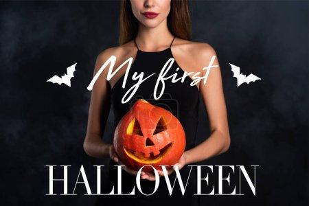 Photo pour Vue recadrée de femme tenant citrouille halloween avec mon premier lettrage Halloween - image libre de droit