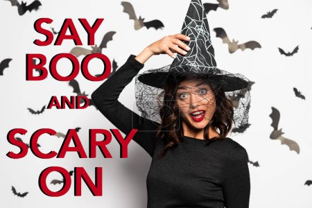 Photo for Crazy woman in witch hat looking at camera in Halloween near say boo and scary on red lettering - Royalty Free Image