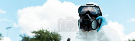Photo for Cleaning specialist in respirator talking on cellphone in park during coronavirus pandemic, panoramic orientation - Royalty Free Image