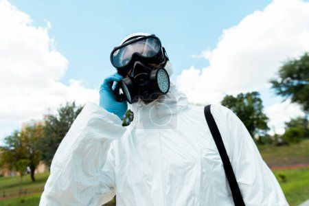 Photo for Cleaning specialist in hazmat suit and respirator talking on cellphone outdoors during covid-19 pandemic - Royalty Free Image