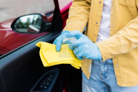 abgeschnittene Ansicht des Mannes in medizinischen Handschuhen mit Antiseptikum und Lappen zur Reinigung des Autos während der Covid-19-Pandemie