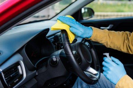 Photo pour Vue partielle de l'homme dans des gants en latex en utilisant un antiseptique et un chiffon pour la désinfection intérieure de la voiture pendant la pandémie de coronavirus - image libre de droit