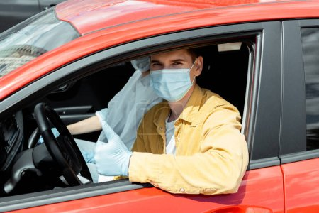 Photo for Man and woman in medical masks and protection gloves sitting in car and showing thumb up during covid-19 pandemic - Royalty Free Image
