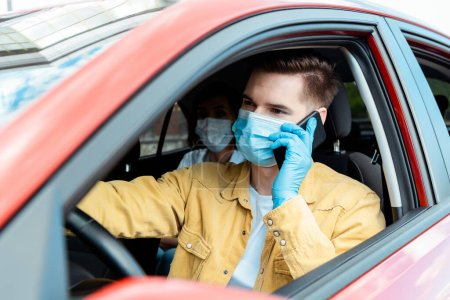 Photo for Male driver in medical mask and gloves talking on phone in taxi with passenger during coronavirus pandemic - Royalty Free Image