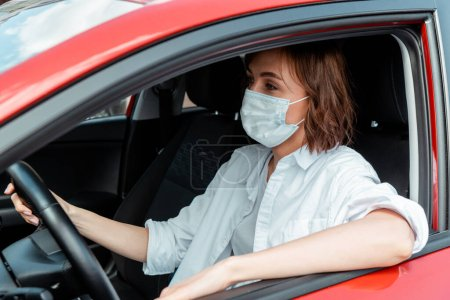 Photo for Woman in medical mask driving car during covid-19 pandemic - Royalty Free Image