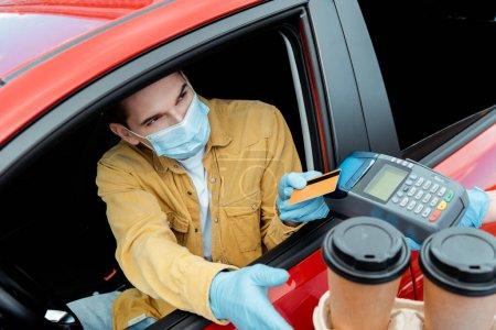 Photo pour Homme en masque médical faisant transaction avec carte de crédit et terminal pour acheter du café à emporter de voiture pendant la pandémie de coronavirus - image libre de droit