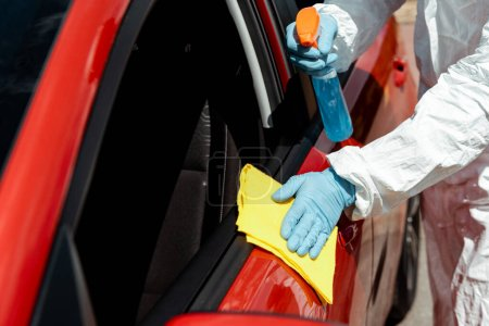 Photo for Cropped view of specialist in hazmat suit cleaning car with disinfectant spray and rag during covid-19 pandemic - Royalty Free Image