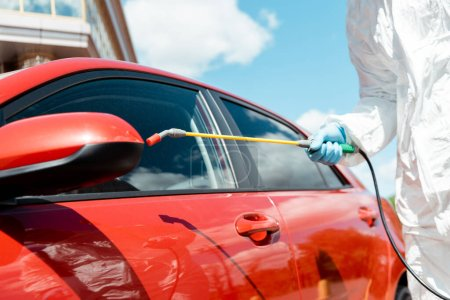 Photo for Cropped view of specialist in hazmat suit cleaning car with disinfectant spray during coronavirus pandemic - Royalty Free Image