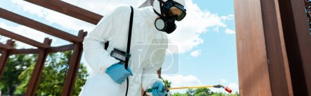 Photo for Workman in hazmat suit and facemask disinfecting wooden construction in park during coronavirus pandemic, horizontal crop - Royalty Free Image