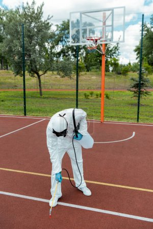 Photo for Specialist in hazmat suit and respirator disinfecting basketball court in park during covid-19 pandemic - Royalty Free Image