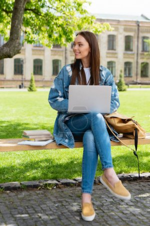 attractive student sitting on bench and using laptop near books, online study concept