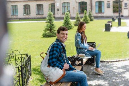 Photo pour Foyer sélectif de joyeux étudiant souriant tandis que la fille en utilisant un ordinateur portable près du campus universitaire, concept d'étude en ligne - image libre de droit