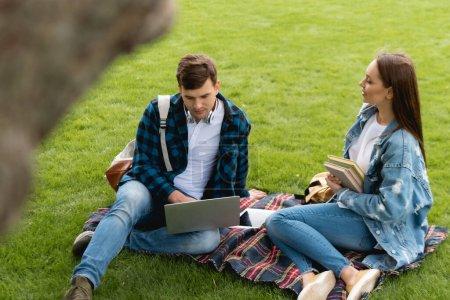 Photo pour Foyer sélectif de gai fille tenant des livres et regardant beau élève à l'aide d'un ordinateur portable, concept d'étude en ligne - image libre de droit
