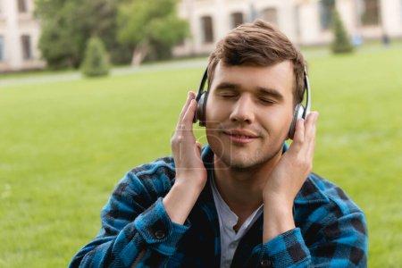 Photo pour Étudiant heureux avec les yeux fermés touchant écouteurs sans fil et écouter de la musique - image libre de droit