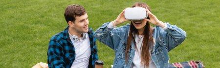 Photo pour En-tête de site Web de joyeux étudiant regardant fille excitée dans le casque de réalité virtuelle - image libre de droit