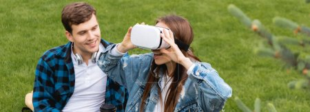 panoramic shot of cheerful student looking at happy girl in virtual reality headset