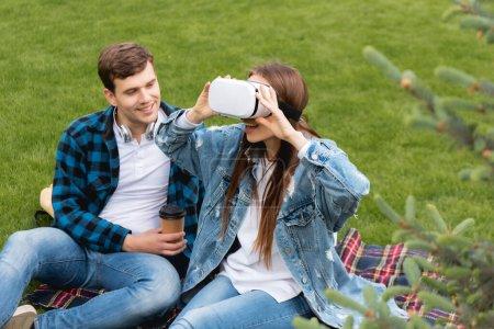 Photo pour Foyer sélectif de joyeux étudiant tenant tasse en papier et regardant fille excitée dans le casque de réalité virtuelle - image libre de droit