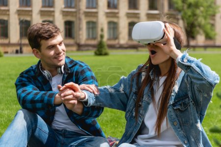 Photo pour Étudiant joyeux tenant la main avec fille surprise dans un casque de réalité virtuelle - image libre de droit