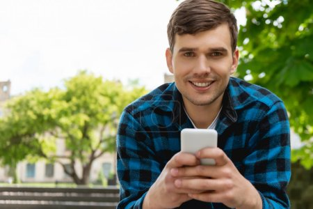 Photo for Happy student smiling while using smartphone - Royalty Free Image