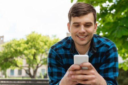 handsome student smiling while using smartphone