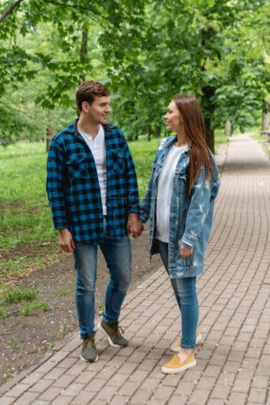 cheerful couple of students holding hands and looking at each other in park