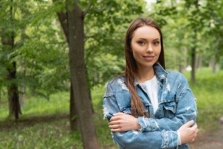 Photo pour Jolie jeune étudiante en jean veste regardant caméra tout en se tenant avec les bras croisés dans le parc - image libre de droit