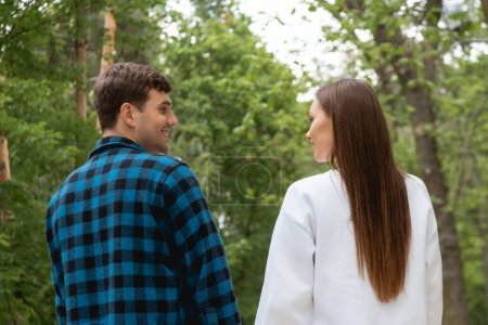 Photo for Handsome boyfriend and girlfriend looking at each other in park - Royalty Free Image